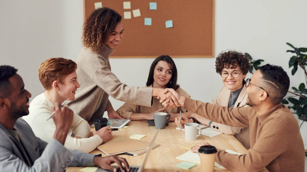 An office meeting. Team members are sitting and woman is standing a shaking a colleague's hand.