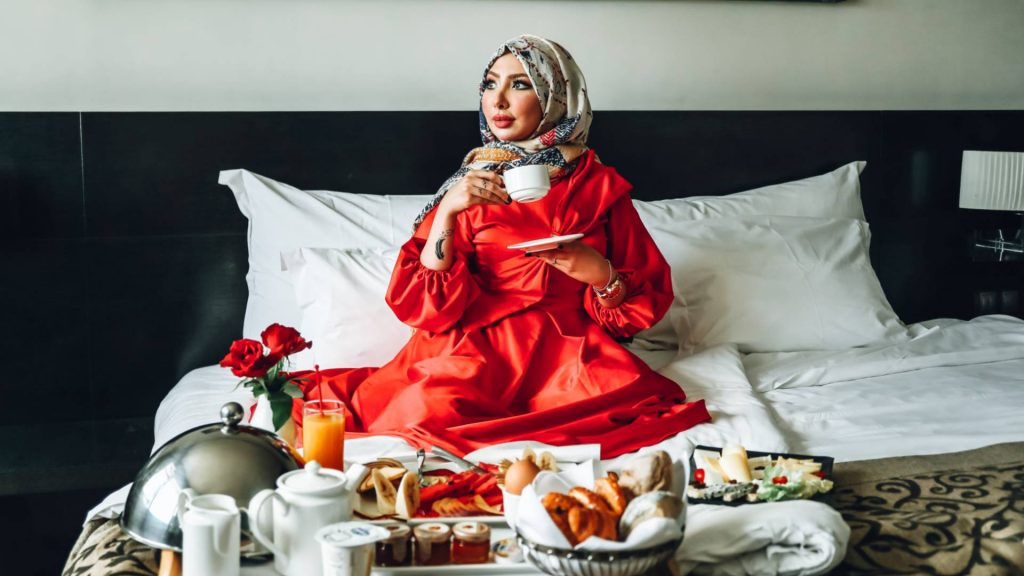 A woman wearing a red gown is having breakfast in bed.