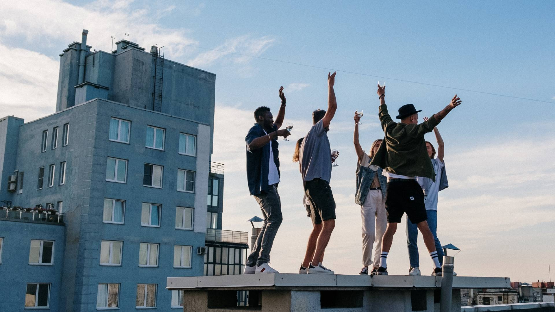 A group of friends celebrate on a rooftop.