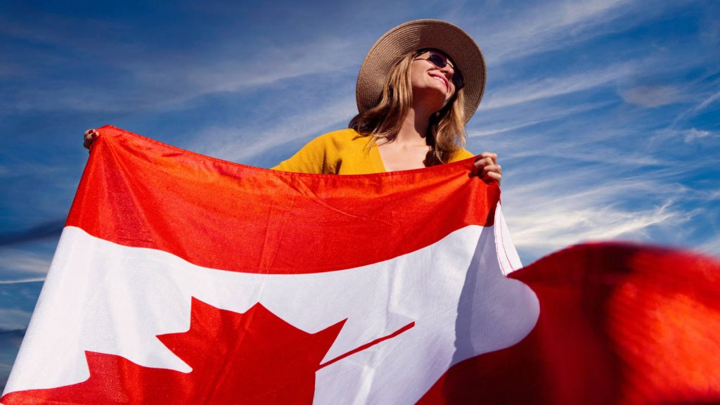 A woman in a hat and sunglasses waves a Canadian flag.