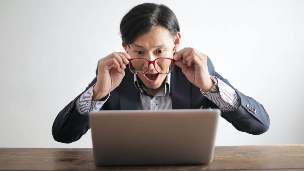 A man looking at his laptop pulls off his glasses in disbelief.