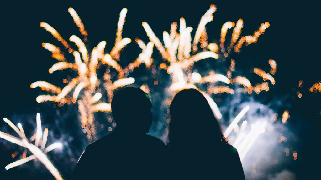 The silhouette of two people watching fireworks.