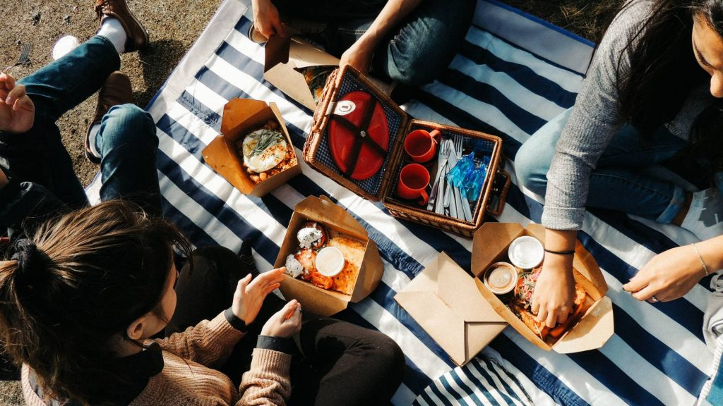 A birds eye view of four friends having a picnic. They sit on a white and blue stripped blanket. There are paper take-away boxes of food and a square picnic basket with a red plate, two red cups and cutlery.