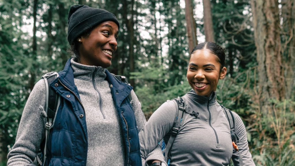 Two women smile at each other while walking through the forest on a hike