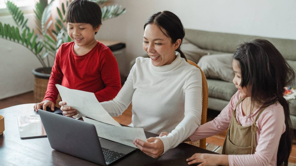 A smiling woman sat at her laptop reviewing papers. Two children stand by her sides.
