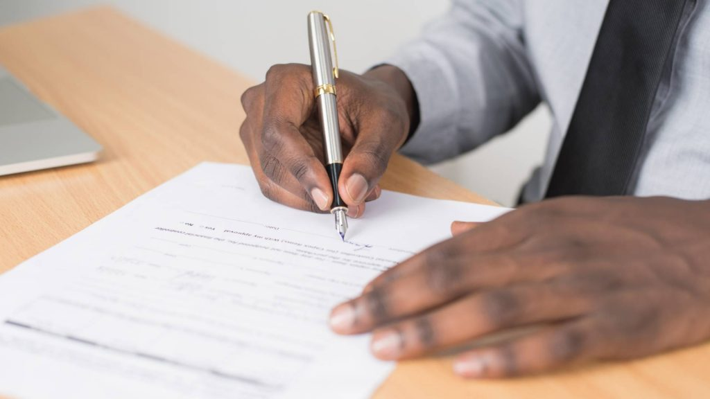 Hands signing a document.