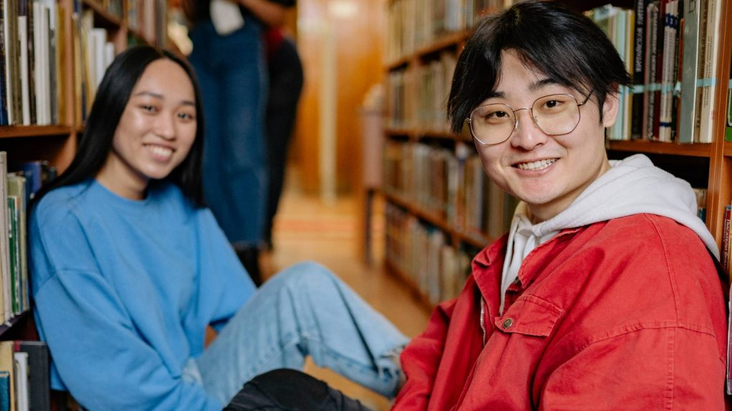 Two smiling students sat on the floor of a library between two rows of book.