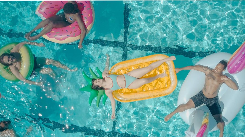 Friends lounging on pool floaties.