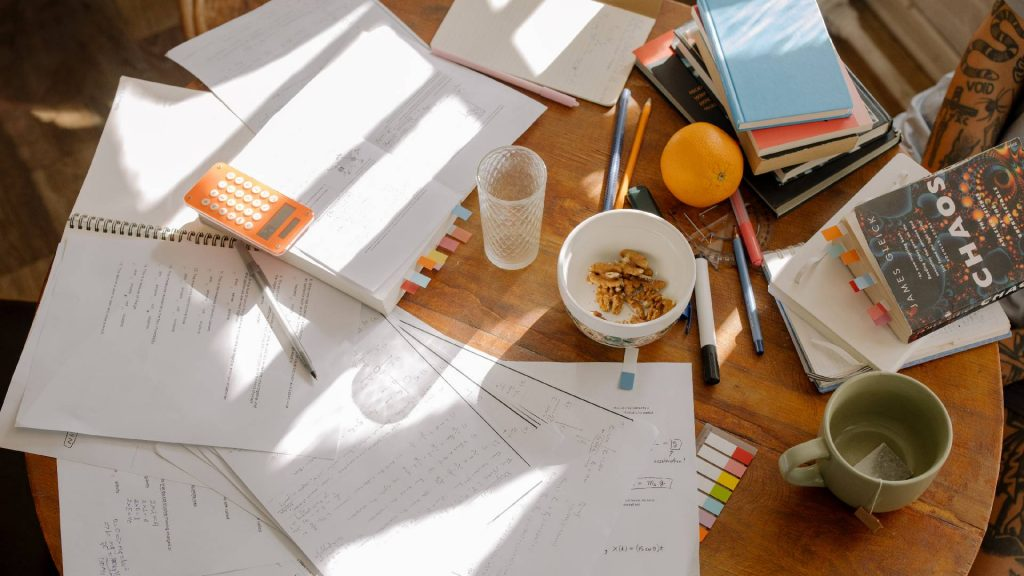 A table cover in study notes, a calculator, pens, books, snacks and cups.