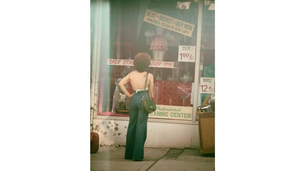 Women in the 80s window shop clothing. The layout of the store is classic.