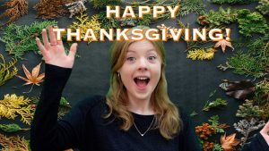 """Taylor excitedly throwing her arms up surrounded by leaves with the words, """"Happy Thanksgiving!"""" overhead."""