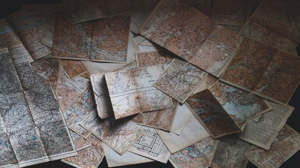 A table with many different maps strewn out across it.