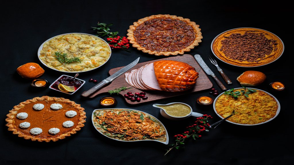 A meal including many different foods traditionally eaten on Thanksgiving, such as roast ham, pumpkin pie, mashed potatos, and more.